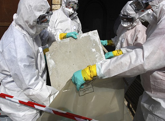 Asbestos abatement team removing dangerous asbestos materials