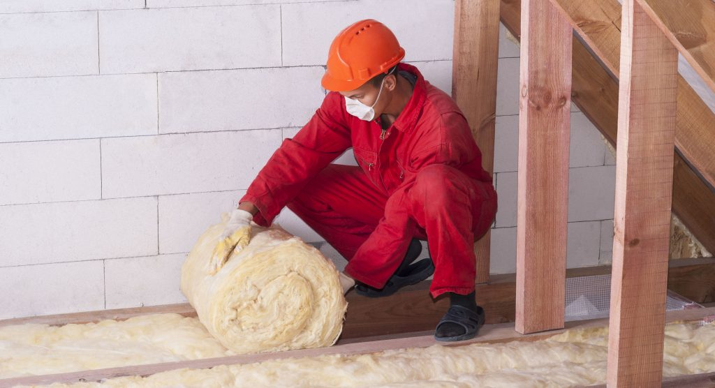 Worker installing insulation in an attic