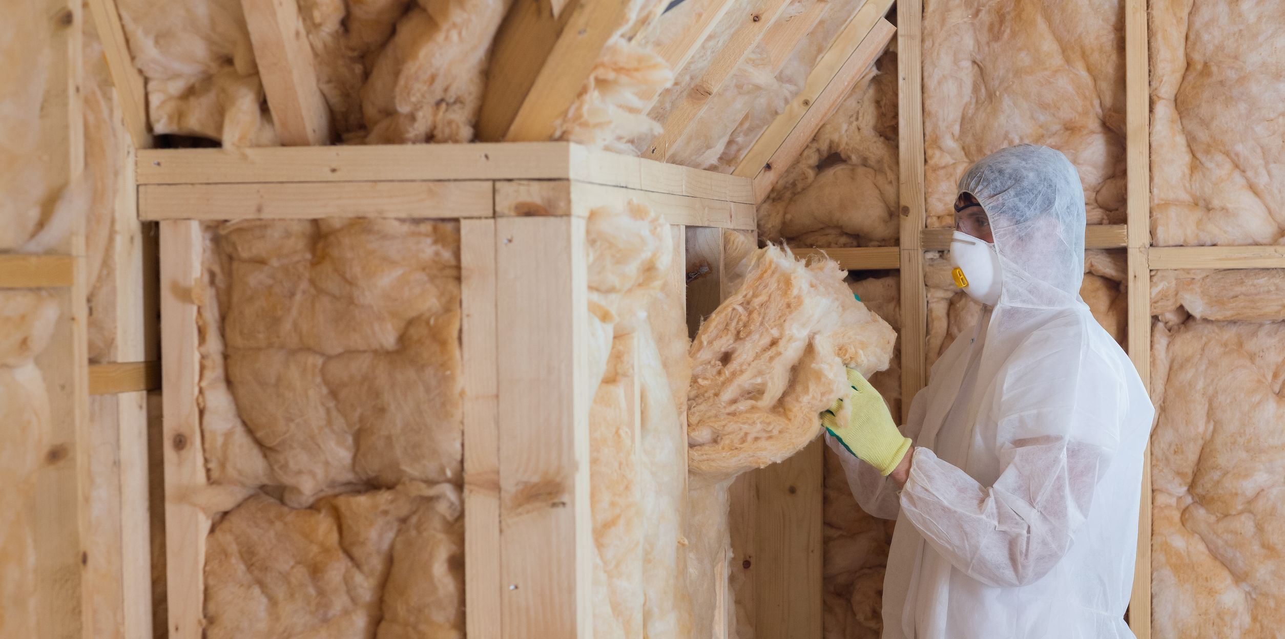 Worker in protective gear holding insulation near exposed wall