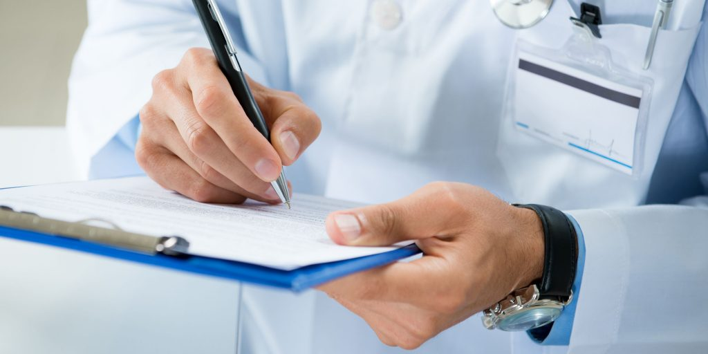 Doctor writing on a notepad