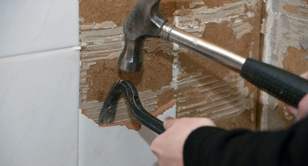 Woman Removing Tile in Home Kitchen