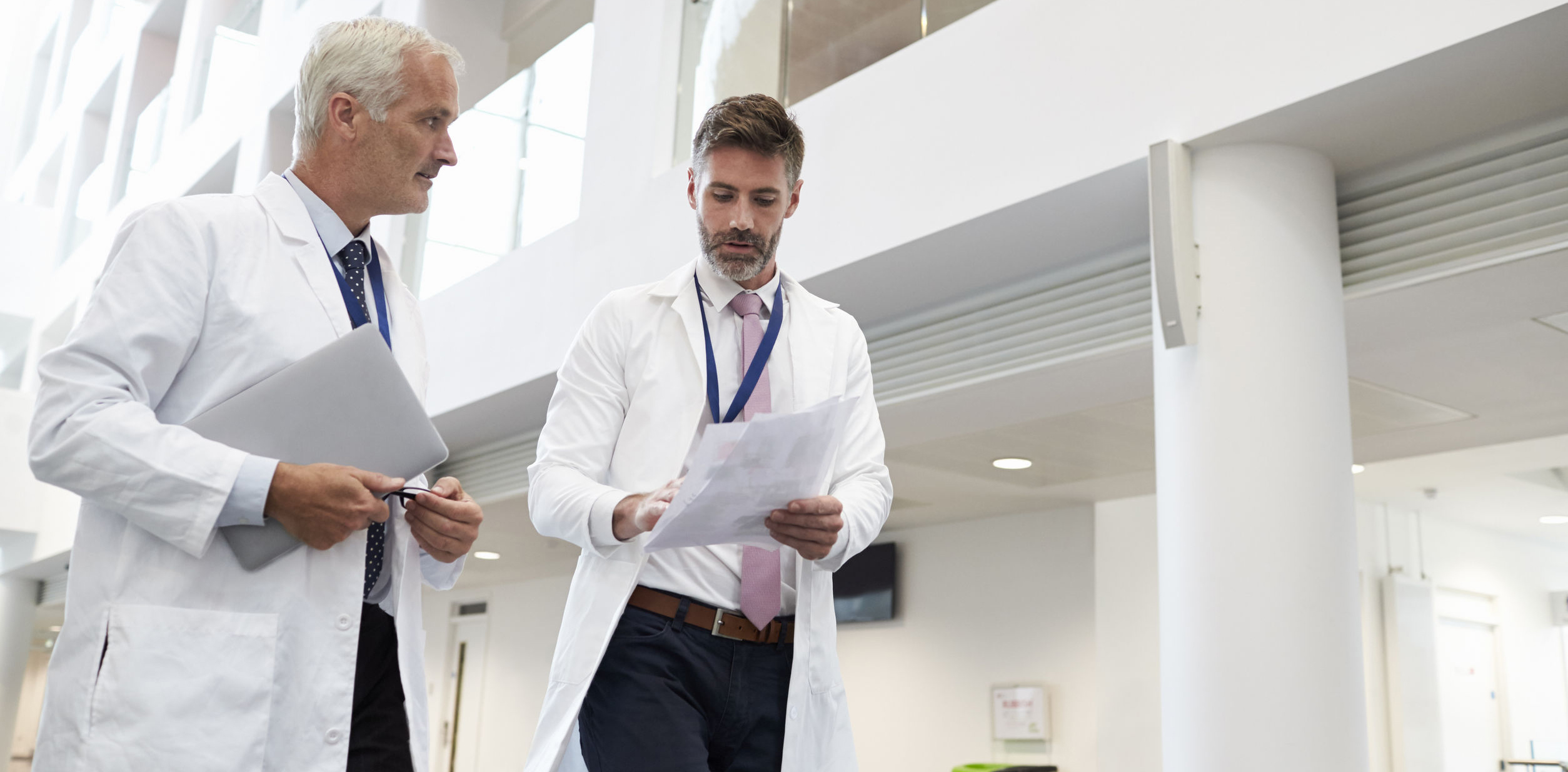 Two Doctors Talking As They Walk Through Modern Hospital