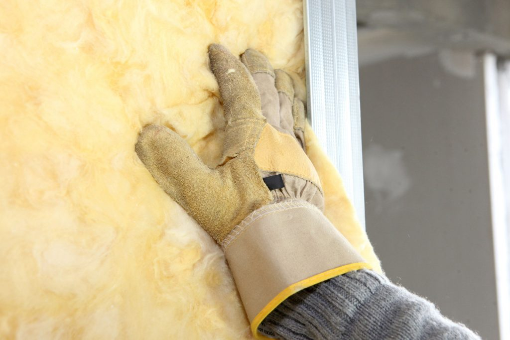 Gloved hand touching insulation