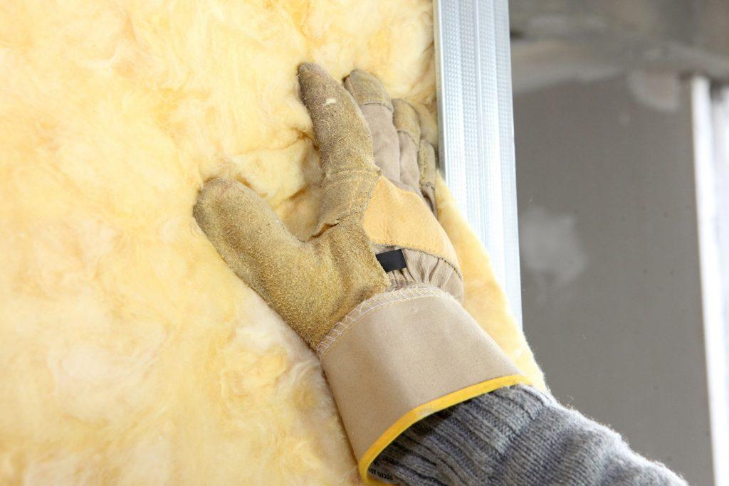 Gloved hand touching insulation