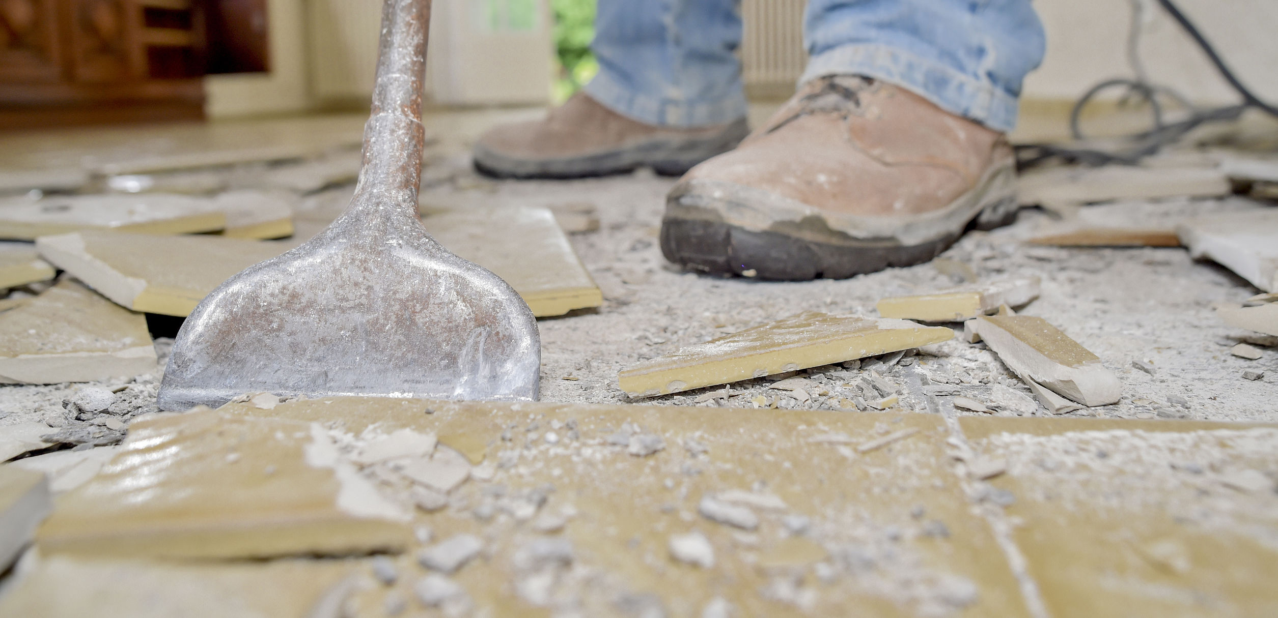 Man removing old floor tiles