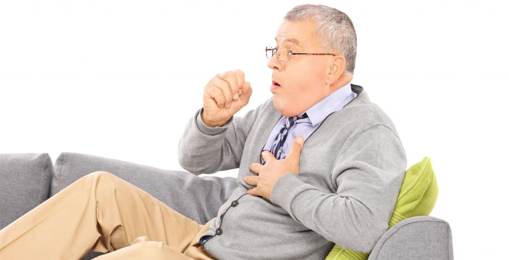 Elderly man sitting on a couch coughing