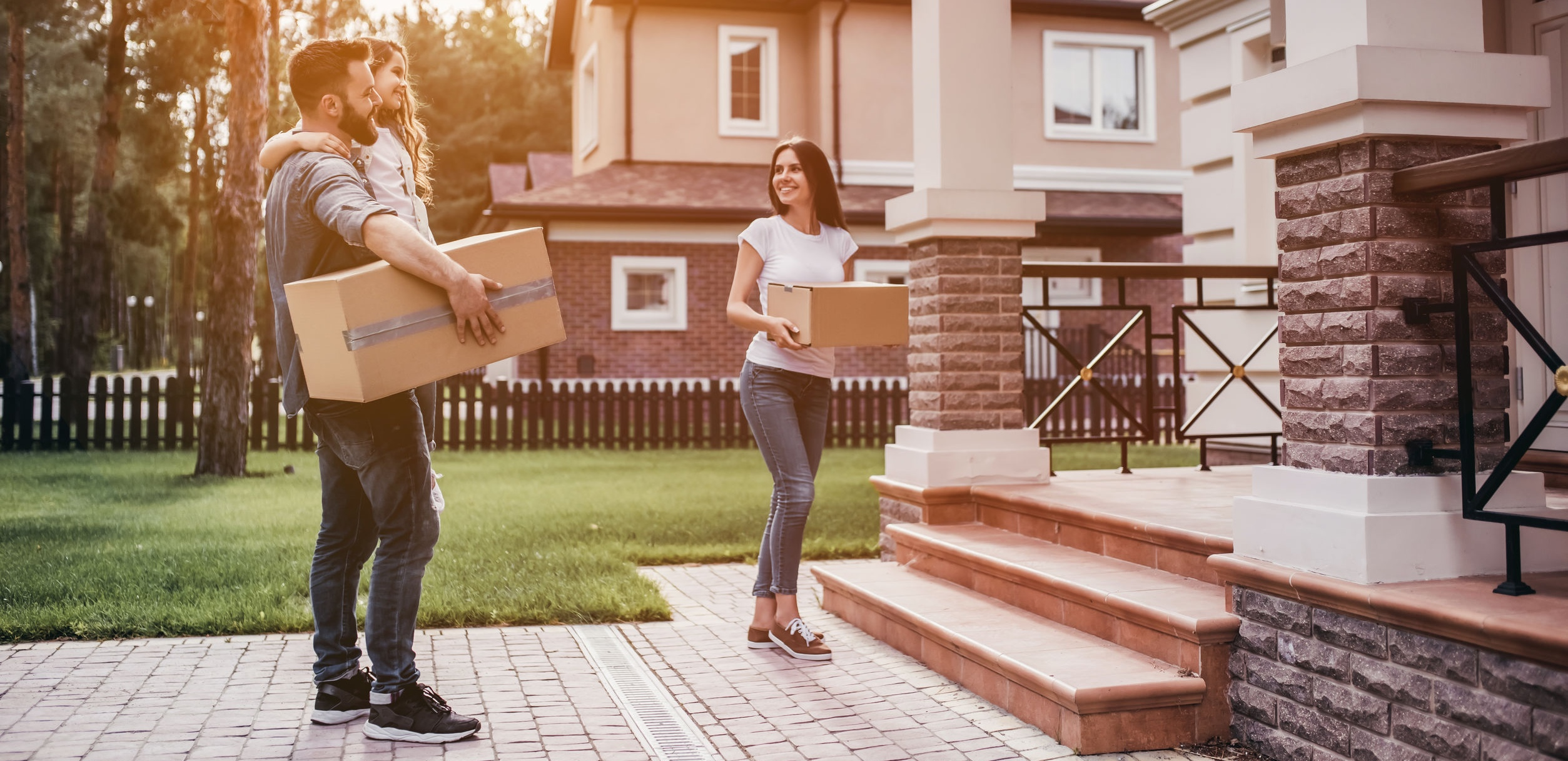 Couple standing near new house with cardboard boxes