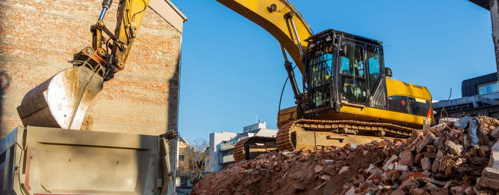 Excavator on a construction site during the demolition of a house