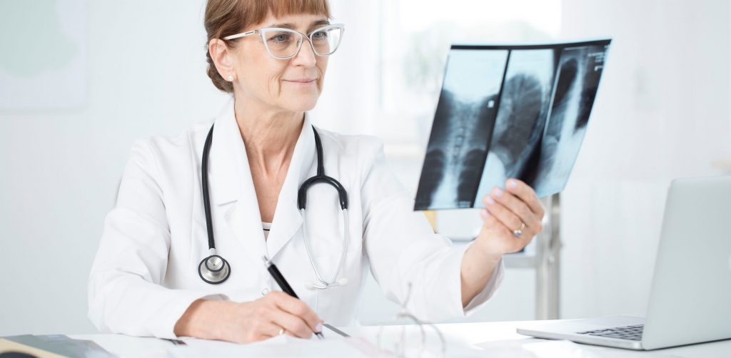 Pulmonologist with stethoscope looking at an X-ray picture of lungs