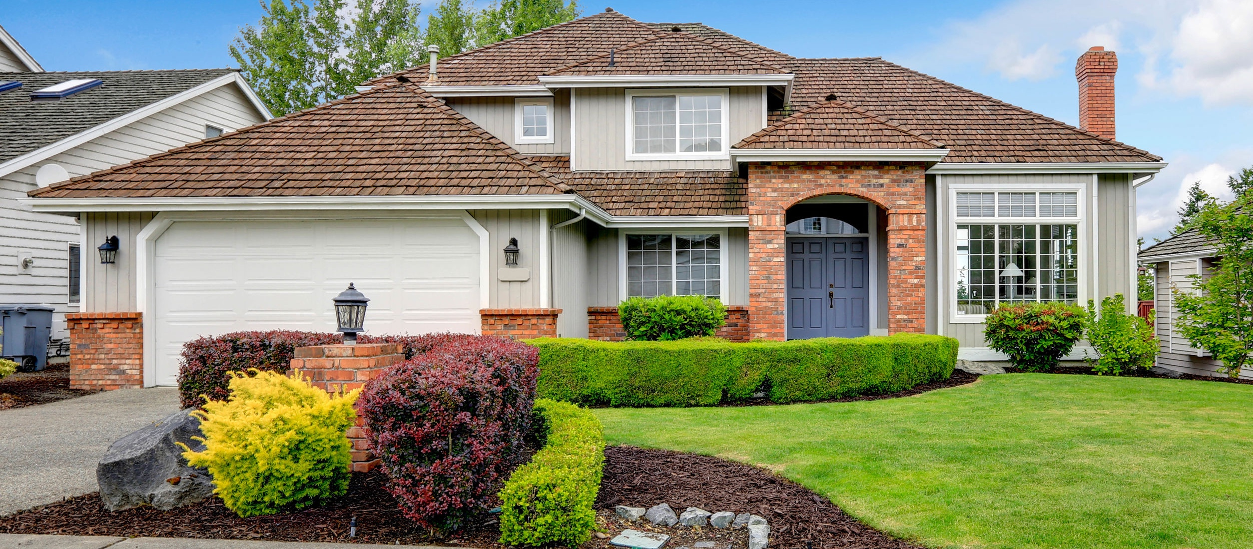 House exterior with brick trimmed entrance porch, green lawn and trimmed hedges, garage with driveway