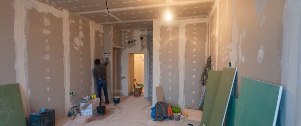 Person installing sheetrock for remodeling project