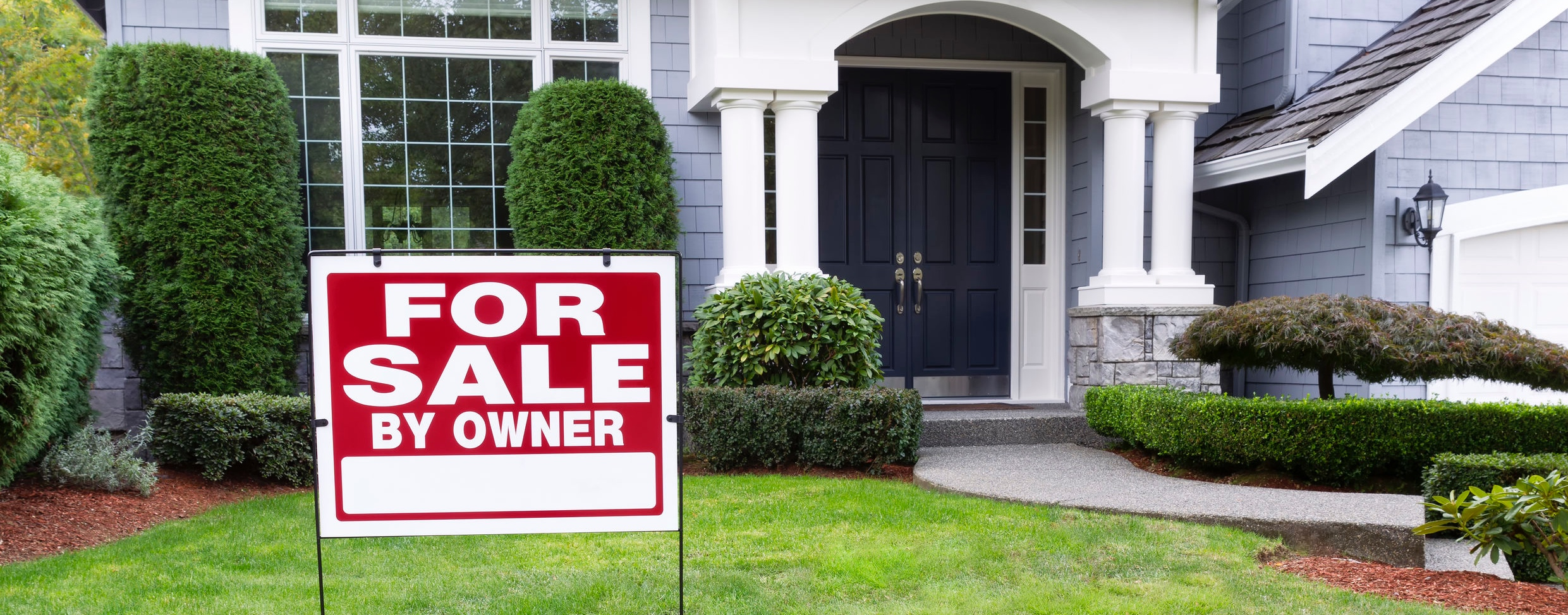 Closeup view of Modern Suburban Home for Sale Real Estate Sign in front