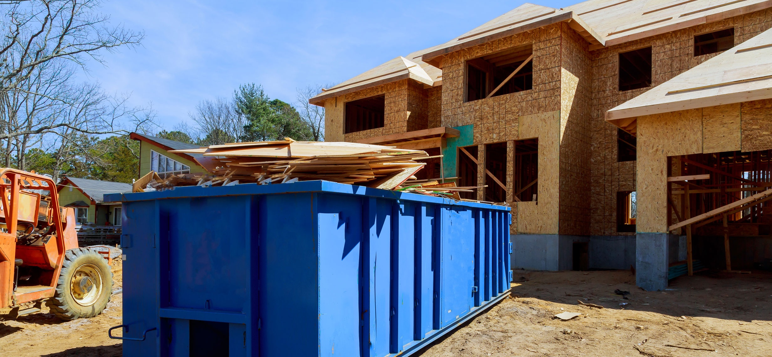 Dumpster and construction materials at building site