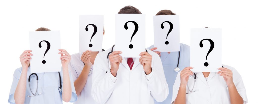 Group Of Doctors Hiding Face With Question Mark Sign Over White Background