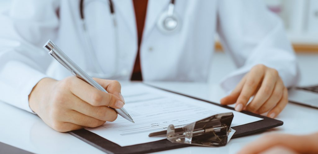 Woman doctor filling up an application form while consulting patient