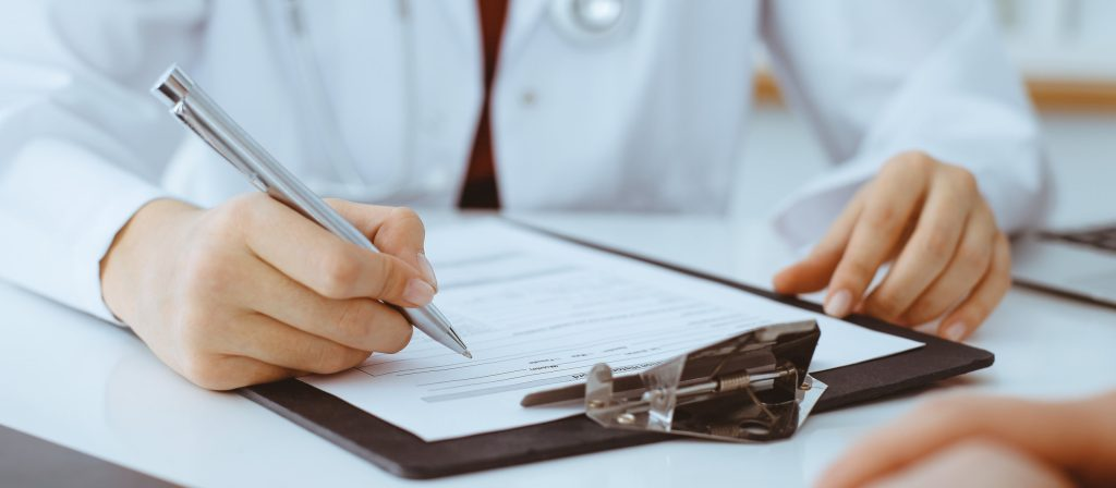 Doctor filling up an application form while consulting patient