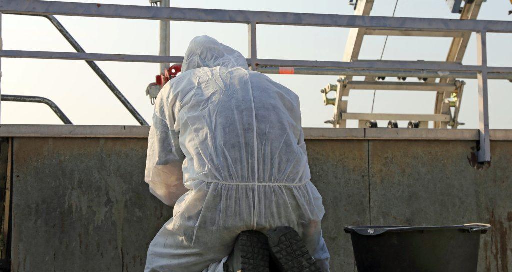 Professional in protective gear performing asbestos abatement