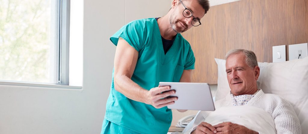 Surgeon With Digital Tablet Visiting Senior Male Patient In Hospital Bed